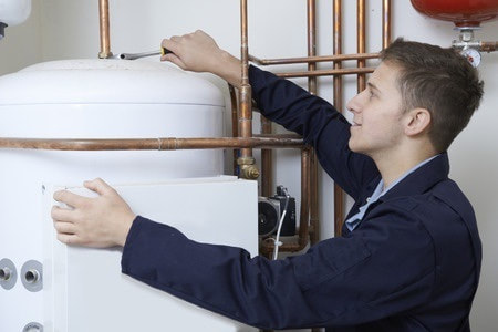 plumber using wrench to fix pipes on top of water heater